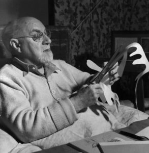 Original Caption: Henri Matisse working on paper cut out. Undated photo.